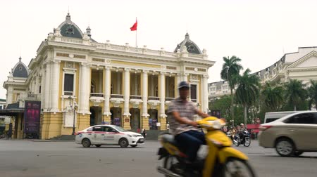 north vietnam : TRAFFIC AND PEOPLE OUTSIDE HANOI OPERA HOUSE, HANOI, VIETNAM – 2 APRIL 2018: Scooters, cars, traffic and people outside Hanoi Opera House, Hanoi, Vietnam