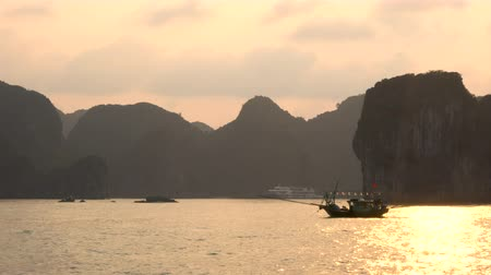 ba : Traditional fishing boat sailing at sunset through the limestone islands in Ha Long Bay, Cat Ba National Park, Vietnam