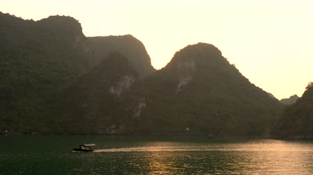 ba : Traditional fishing boat sailing at sunset through the limestone islands, Ha Long Bay, Cat Ba National Park, Vietnam Stock Footage