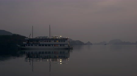 ba : Cruise Boat noored at dusk in the limestone islands of UNESCO World Heritage site, Ha Long Bay, Cat Ba National Park, Vietnam Stock Footage