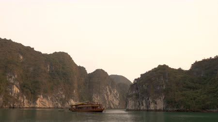 ba : CRUISE BOAT IN HA LONG BAY AT SUNSET, CAT BA NATIONAL PARK, NORTH EAST VIETNAM 4 APRIL 2018 The limestone islands in UNESCO World Heritage site, Ha Long Bay, Cat Ba National Park, Vietnam