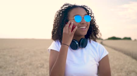 felnőtt : Slow motion follow shot video of beautiful mixed race African American girl teenager young woman in white T-shirt and blue sunglasses walking and talking on her cell phone Stock mozgókép