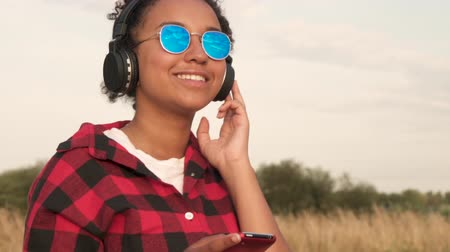Slow motion video of beautiful mixed race African American girl teenager young woman wearing blue sunglasses listening to music on her cell phone and wireless headphones