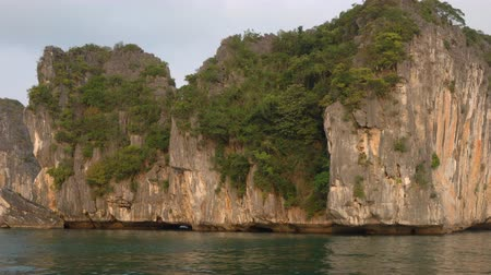 ba : Tracking panning shot from cruise boat sailing through the limestone islands, Ha Long Bay, Cat Ba National Park, Vietnam