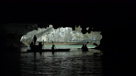 dark island : Tourists in traditional local boats and kayaks exploring the caves of the limestone islands of Ha Long Bay, Cat Ba National Park, Vietnam