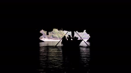 vezetett : Tourists in traditional local boats being guided through the caves of the limestone islands of Ha Long Bay, Cat Ba National Park, Vietnam Stock mozgókép