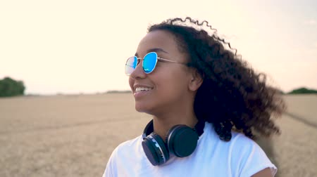 Slow motion follow shot video of beautiful mixed race African American girl teenager young woman in white T-shirt and blue sunglasses walking using her cell phone and wearing wireless headphones
