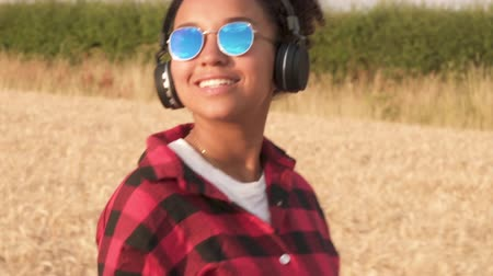 ırklararası : Slow motion tracking video clip of beautiful mixed race African American girl teenager young woman wearing blue sunglasses walking listening to music on wireless headphones at sunset or sunrise