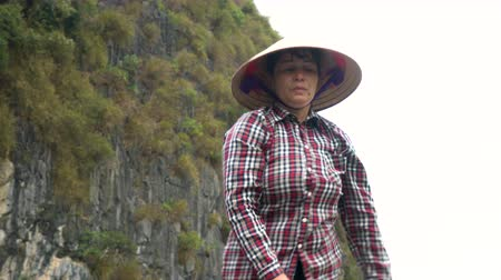 ba : LOCAL WOMAN PADDLING TRADITIONAL BOAT, HA LONG BAY, CAT BA NATIONAL PARK, VIETNAM – 5 APRIL 2018 Local woman wearing conical leaf hat in traditional boat in UNESCO World Heritage site, Ha Long Bay, Vietnam Stock Footage