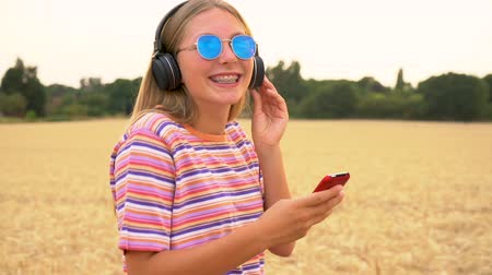 braces : Slow motion tracking video clip of pretty blonde girl teenager young woman wearing a striped t- shirt and blue sunglasses walking listening to music on her cell phone and wireless headphones Stock Footage