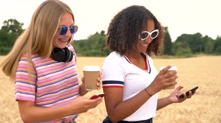 aparat ortodontyczny : Slow motion tracking video clip of pretty blonde girl and mixed race teenager young women wearing sunglasses drinking coffee and using mobile cell phones