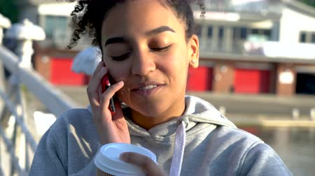 межрасовый : 4K video clip of beautiful mixed race African American girl teenager young woman on a bridge over a river, drinking takeout coffee smiling, laughing and looking to camera