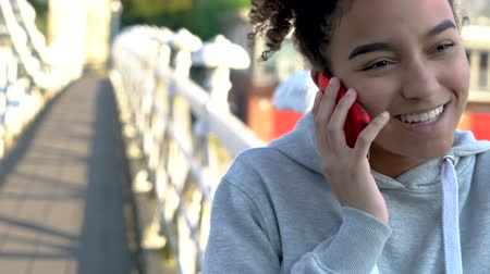 межрасовый : 4K video clip of beautiful mixed race African American girl teenager young woman on a bridge over a river, talking on a mobile cell phone Стоковые видеозаписи