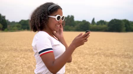 Slow motion tracking video clip of beautiful mixed race African American girl teenager young woman wearing a white t-shirt and blue sunglasses walking listening to music on wireless headphones at sunset or sunrise