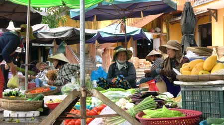 south asian food : LOCAL WOMEN SELLING FOOD VEGETABLES AT HOI AN MARKET, VIETNAM – 6 APRIL 2018: Local women stall holders and people on the daytime streets at Hoi An Market, Vietnam