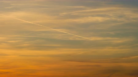 Jet airliner airplane or aeroplane flying leaving a vapor trail across a sunset or sunrise sky Dostupné videozáznamy