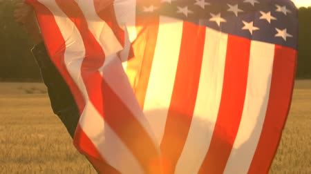 4K video clip of mixed race African American girl teenager female young woman holding an American USA Stars and Stripes flag in a wheat field at sunset or sunrise