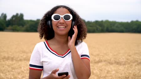 Slow motion video of beautiful mixed race African American girl teenager young woman wearing white sunglasses listening to music on her smart cell phone and wireless headphones