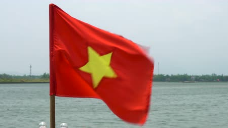 hoi an : Vietnamese flag flying in the wind on a boat on the Thu Bon River, Hoi An, Vietnam, South East Asia
