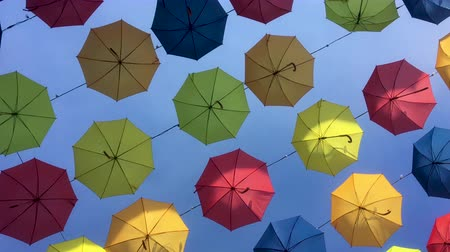 asma : 4K tracking shot of multicolored umbrellas suspended on wires.