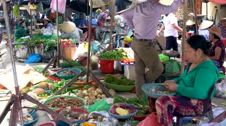 hoi an : LOCAL WOMEN SELLING FOOD VEGETABLES AT HOI AN MARKET, VIETNAM – 6 APRIL 2018: Local women stall holders and people on the daytime streets at Hoi An Market, Vietnam