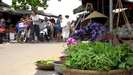hoi an : LOCAL WOMAN IN TRADITIONAL CLOTHES SELLING VEGETABLES AT HOI AN MARKET, VIETNAM – 6 APRIL 2018: Local woman stall holder selling vegetables on the daytime streets at Hoi An Market, Vietnam Stock Footage