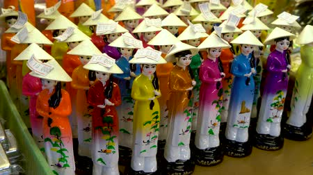 Vietnamese women china figurines, wearing traditional female clothing, for sale in Saigon market, Vietnam Dostupné videozáznamy