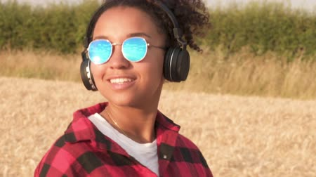 Slow motion tracking video clip of beautiful mixed race African American girl teenager young woman wearing blue sunglasses walking listening to music on wireless headphones Dostupné videozáznamy