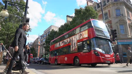 PEOPLE CROSSING OXFORD STREET, LONDON, ENGLAND – 25 SEPTEMBER 2018: 4K video of pedestrian crossing, traffic, taxis and red double decker London buses in Oxford Street, London, England