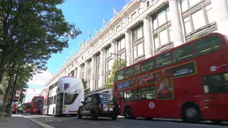 london cab : SELFRIDGES DEPARTMENT STORE, OXFORD STREET, LONDON, ENGLAND – 25 SEPTEMBER 2018: Slow moving queuing traffic, taxis and red double decker London buses driving past Selfridges, Oxford Street, London, England