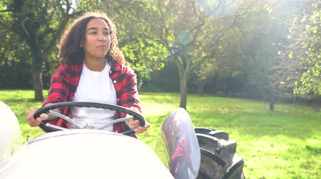 межрасовый : Beautiful African American mixed race teenage girl young woman driving a gray tractor through a sunny apple orchard eating an apple