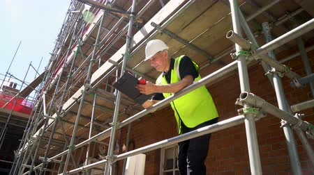 ev idaresi : Male builder foreman, worker, surveyor or architect working on construction building site standing on scaffolding writing on clipboard and talking on cell phone