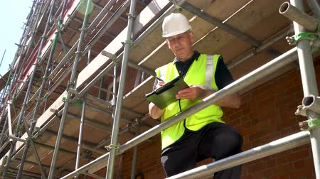 ev idaresi : Male builder foreman, construction worker, surveyor, or architect working on construction building site standing on scaffolding writing on clipboard