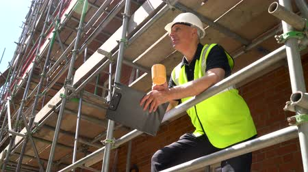 Male builder foreman, surveyor, worker or architect working on construction building site standing on scaffolding with a clipboard and drinking mug of tea or coffee Dostupné videozáznamy