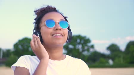 Slow motion tracking video of beautiful mixed race African American girl teenager young woman walking in a field, wearing a white t-shirt and sunglasses listening to music on her cell phone and wireless headphones