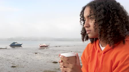 Beautiful mixed race African American girl teenager young woman wearing orange hoodie, drinking takeout coffee by a harbor looking sad or thoughtful