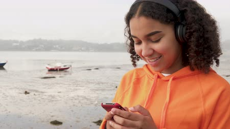 Beautiful mixed race African American girl teenager young woman wearing orange hoodie, sitting on a sea front using her smart cell phone for social media or texting