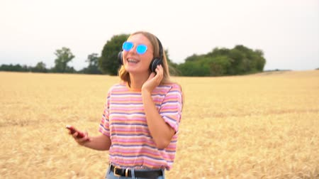 tracking : Slow motion tracking video clip of pretty blonde girl teenager young woman wearing a striped t- shirt and blue sunglasses walking listening to music on her cell phone and wireless headphones Stock Footage