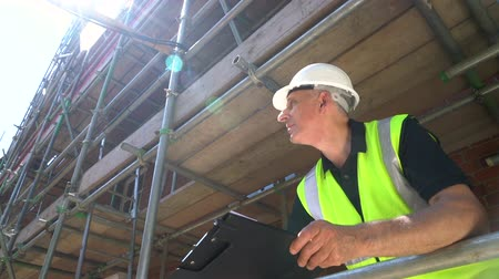 Male builder foreman, construction worker, surveyor, or architect working on construction building site standing on scaffolding writing on clipboard