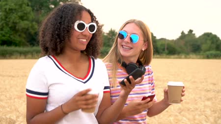 навынос : Slow motion tracking video clip of pretty blonde girl and mixed race teenager young women wearing sunglasses drinking coffee and using mobile cell smart phones for social media Стоковые видеозаписи