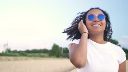 Slow motion follow shot video of beautiful mixed race African American girl teenager young woman in white T-shirt and blue sunglasses walking listening to music on wireless headphones