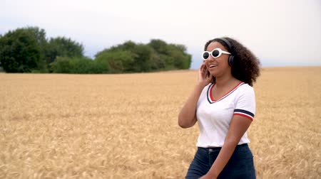 Slow motion tracking video clip of beautiful mixed race African American girl teenager young woman wearing white sunglasses walking listening to music on wireless headphones