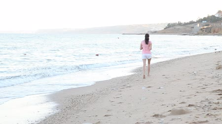 longhair : girl in the morning runs along the beach near the sea
