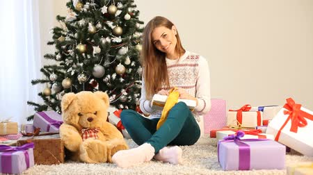 fireplace : the girl sitting by the Christmas tree and Christmas gifts