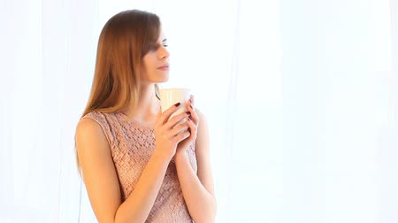 indian tea : girl drink hot tea or coffee while standing at the window
