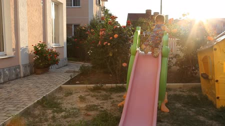 desfocagem : the little boy playing in the playground slides down from a hill Stock Footage