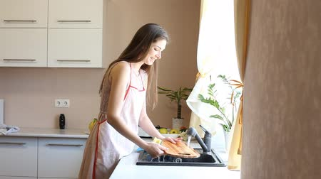 домохозяйка : girl housewife is washing dishes in the kitchen