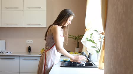 szobalány : girl housewife is washing dishes in the kitchen