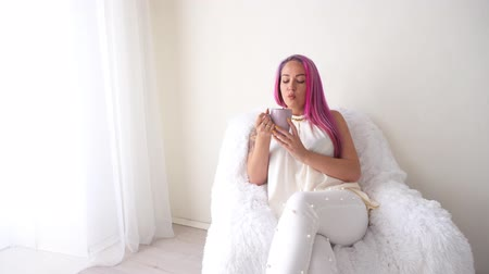armchairs : the girl with the pink hair is sitting in a white armchair drinking coffee or tea Stock Footage