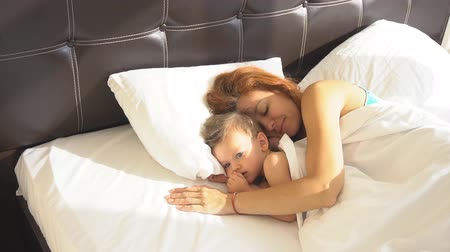 пробуждение : mom with son baby woke up in the morning on the bed